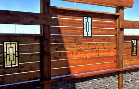 Treated wood privacy screen with stone cladding and metal insert
